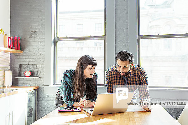 Man and woman using laptop computer while standing at table in office