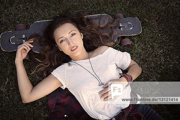 Draufsicht einer Frau  die mit dem Kopf auf einem Skateboard liegt  während sie auf einem Grasfeld liegt