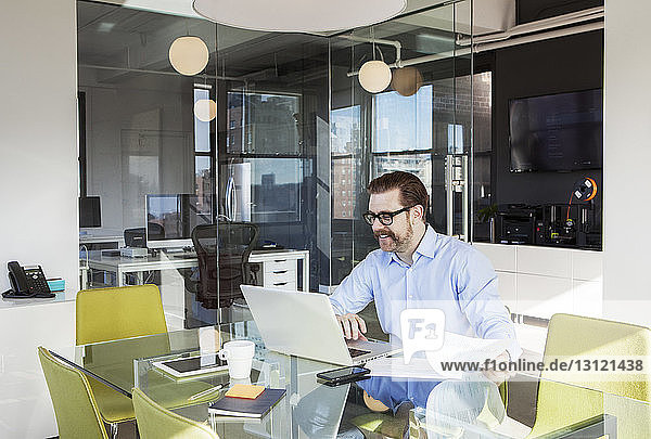 Happy businessman using laptop at conference table in board room