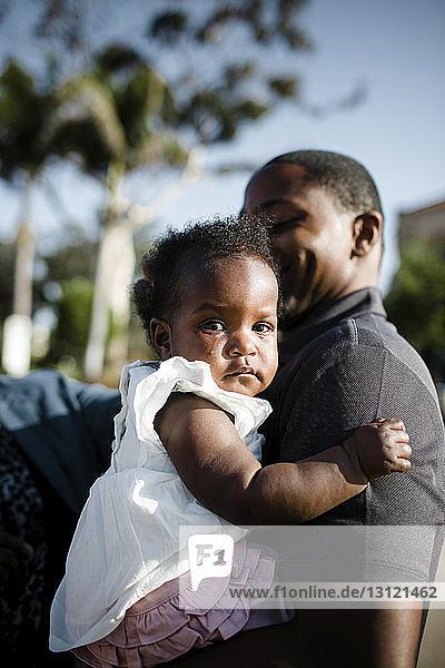 Vater trägt weinende Tochter  während er am Himmel steht