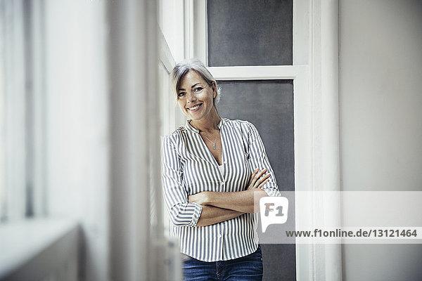 Porträt einer glücklichen reifen Geschäftsfrau  die im kreativen Büro die Arme durch ein Fenster verschränkt