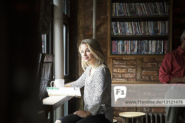 Portrait of smiling woman with newspaper having coffee at cafe