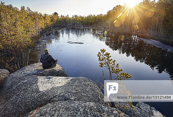 Rückansicht eines Mannes  der meditiert  während er bei Sonnenaufgang auf einer Felsformation am See im Wald sitzt