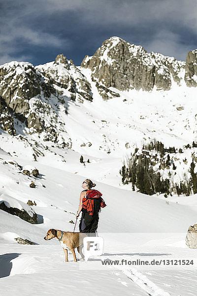 Wanderin mit Hund steht vor schneebedecktem Berg