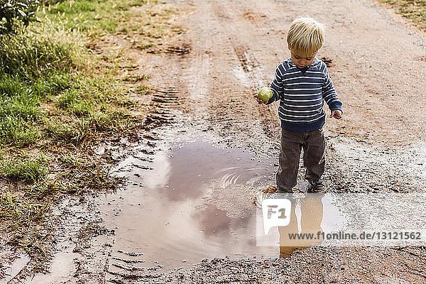 Junge mit Apfel steht in schmutziger Pfütze