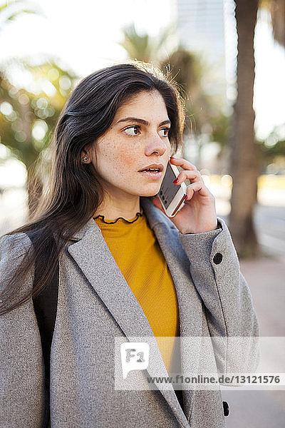 Junge Frau trägt einen Mantel  während sie in der Stadt an ein Smartphone geht