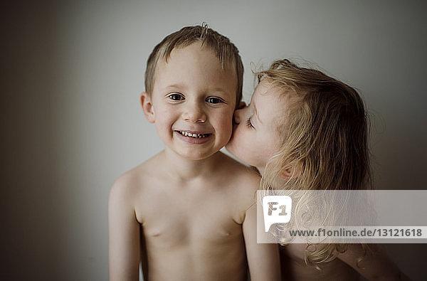 Porträt eines hemdlosen Bruders  der zu Hause von seiner Schwester geküsst wird