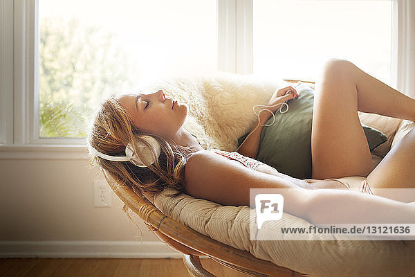 Relaxed woman listening music while lying on sofa at home