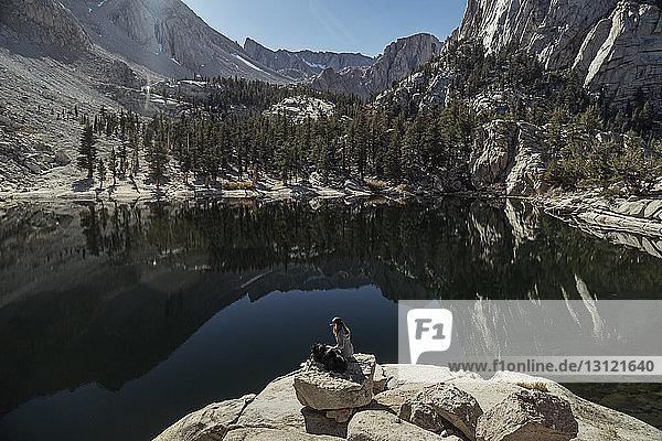 Hochwinkelaufnahme einer Frau mit Hund  die am sonnigen Tag auf einem Felsen am See sitzt