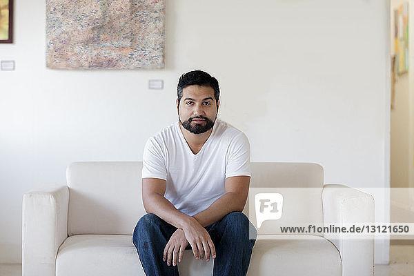 Portrait of artist sitting on sofa against white wall in art studio
