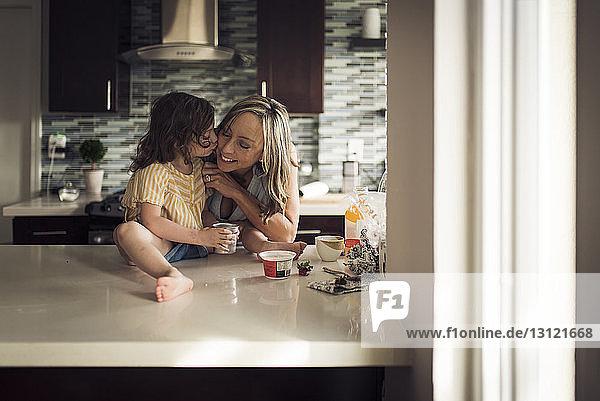 Mädchen küsst Mutter  die zu Hause auf dem Küchentisch sitzt