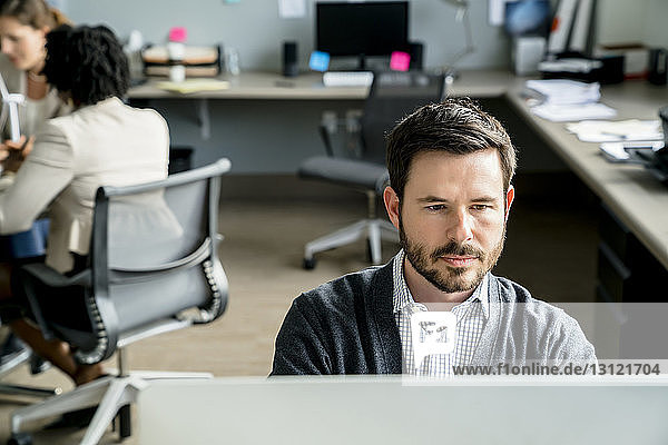 Geschäftsmann benutzt Desktop-Computer  während Kollegen im Hintergrund diskutieren