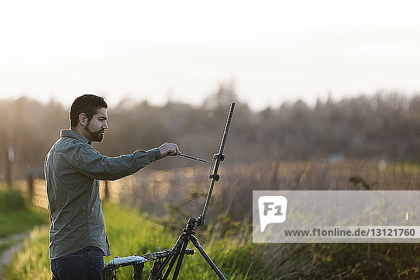Side view of painter painting on canvas at field