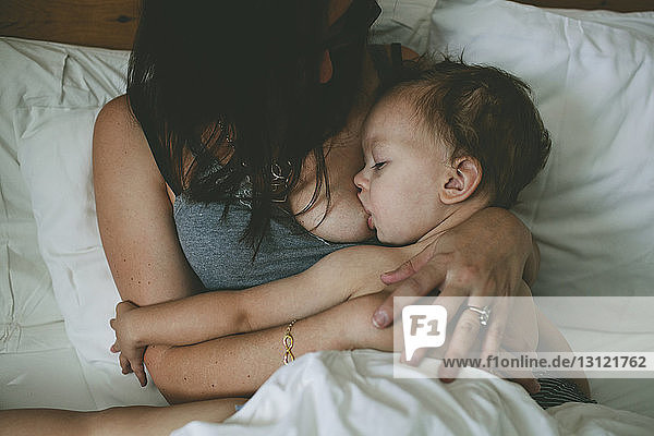 High angle view of mother breastfeeding boy while lying on bed at home
