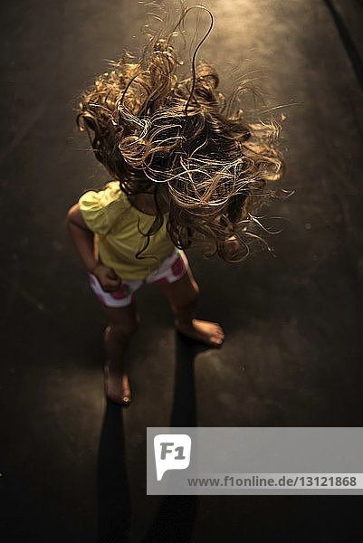 High angle view of girl with tousled hair standing on trampoline
