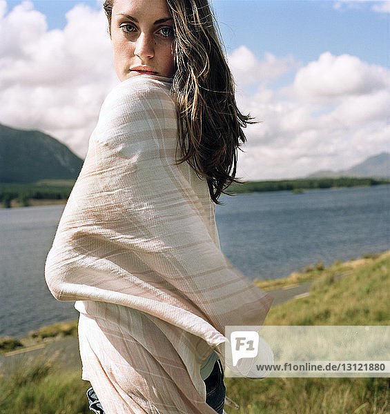 Portrait of confident young woman wrapped in scarf standing on lakeshore