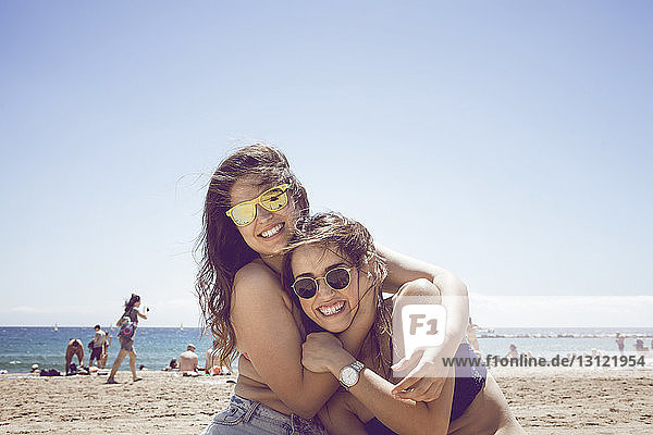 Happy friends embracing at beach against clear sky