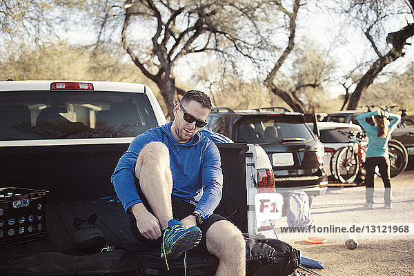 Man wearing sports shoe while sitting in pick-up truck