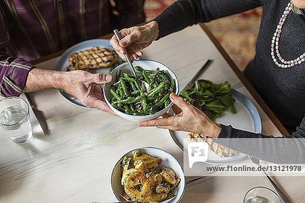 Ein Mann gibt einer Frau am Esstisch eine Schüssel mit gekochten grünen Bohnen