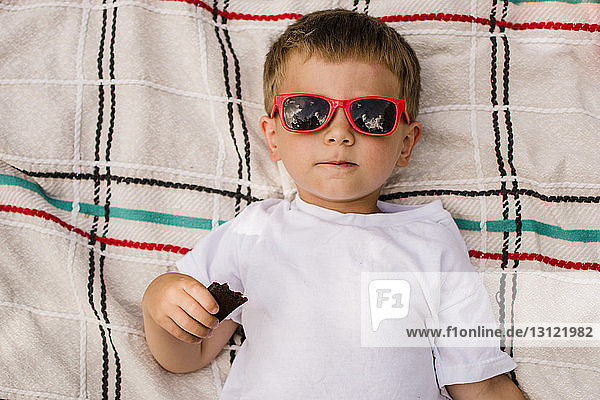 Hochwinkelaufnahme eines Jungen mit Sonnenbrille  der auf einer Decke liegend Schokolade hält
