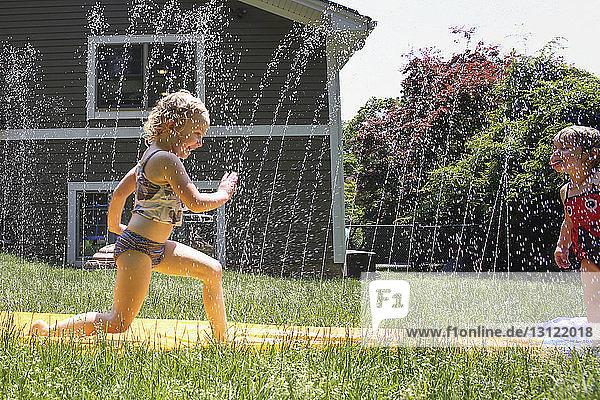 Glückliche Geschwister spielen mit Wasser auf dem Grasfeld im Hinterhof