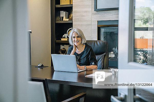Porträt einer lächelnden Geschäftsfrau  die am Laptop-Computer am Schreibtisch im Büro arbeitet  durch die Tür gesehen