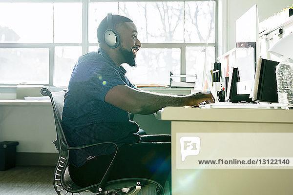 Seitenansicht eines lächelnden Geschäftsmannes  der einen Desktop-Computer benutzt  während er am Schreibtisch im Büro arbeitet