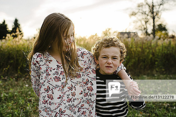 Portrait of brother making face while standing by sister at park