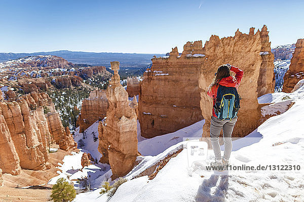 Rear view of hiker standing on snow covered mountain at Bryce Canyon National Park