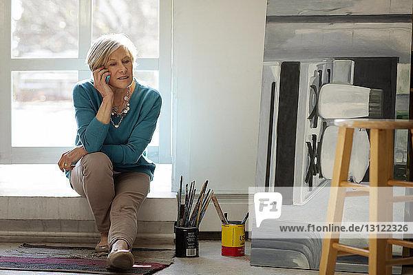 Frau benutzt Mobiltelefon  während sie zu Hause auf dem Fensterbrett sitzt