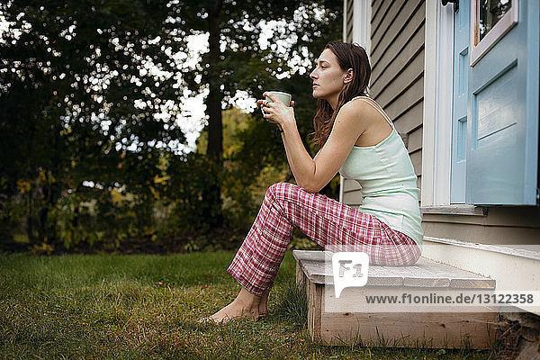 Seitenansicht einer nachdenklichen Frau  die eine Kaffeetasse hält  während sie vor dem Haus sitzt