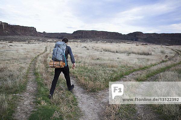 Rear view of hiker walking on field against sky