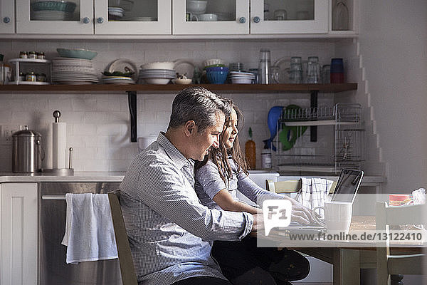 Daughter sitting with father using laptop computer in kitchen at home