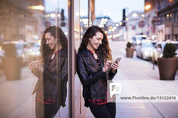 Lächelnde junge Frau  die ein Smartphone benutzt  während sie auf einem Fußweg an Gebäuden steht
