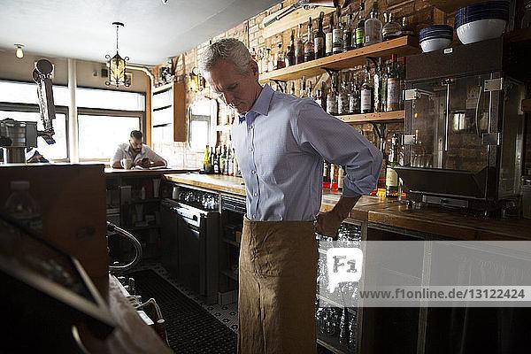 Besitzer trägt Schürze am Bartresen im Café