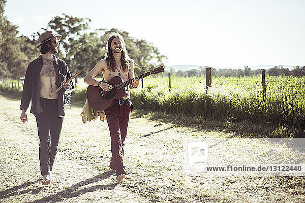 Happy friends playing musical instruments on dirt road by grassy field against sky