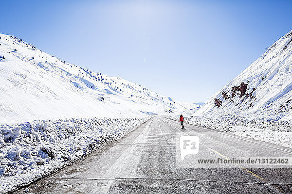Mitteldistanzansicht eines Wanderers  der im Joshua-Tree-Nationalpark auf der Straße durch schneebedeckte Berge läuft