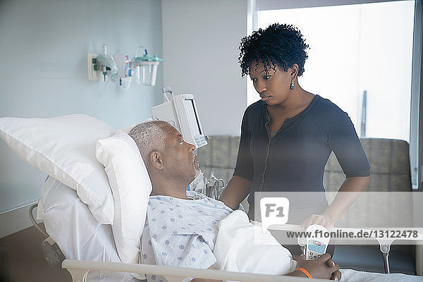 Vater spricht mit Tochter  während er im Bett auf der Krankenstation liegt und durch das Fenster gesehen wird