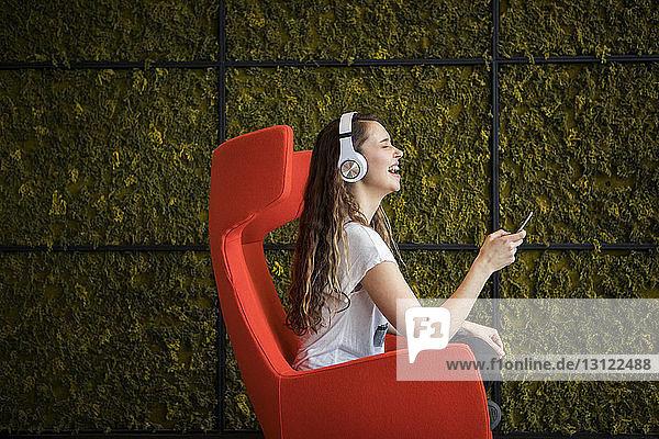 Fröhliche Frau benutzt Smartphone  während sie zu Hause auf einem Sessel sitzt