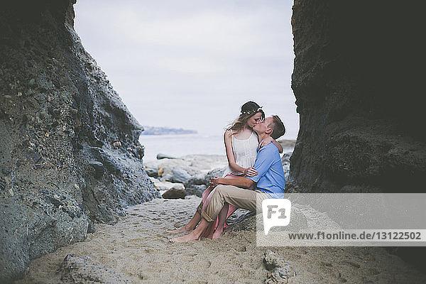 Romantisches Paar küsst sich am Strand auf einem Felsen sitzend