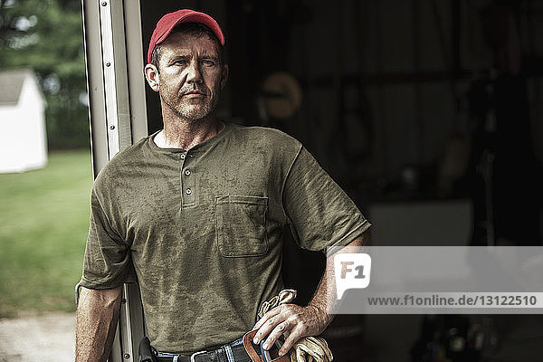 Portrait of confident farm worker standing against barn on sunny day