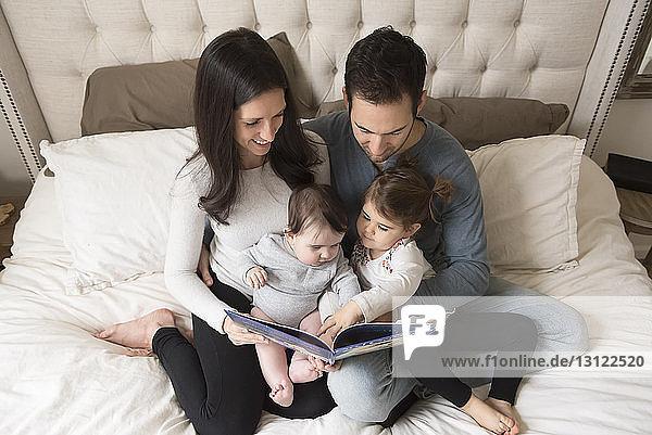 Hochwinkelansicht von Eltern mit Kindern  die auf dem Bett sitzend ein Bilderbuch betrachten