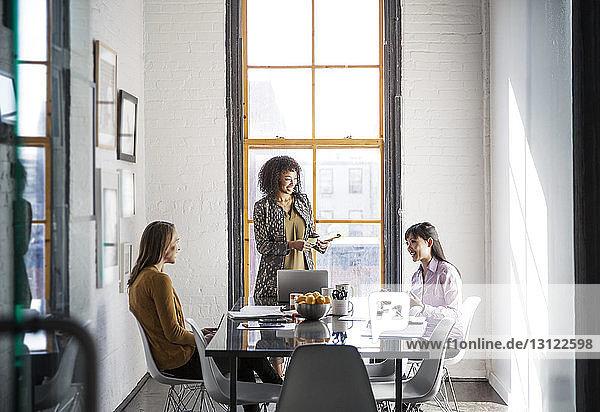 Geschäftsfrauen diskutieren am Tisch gegen Fenster im Kreativbüro