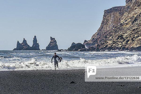 Mann mit Surfbrett am schwarzen Strand bei klarem Himmel am sonnigen Tag