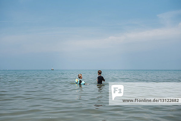 Brothers standing in sea against sky