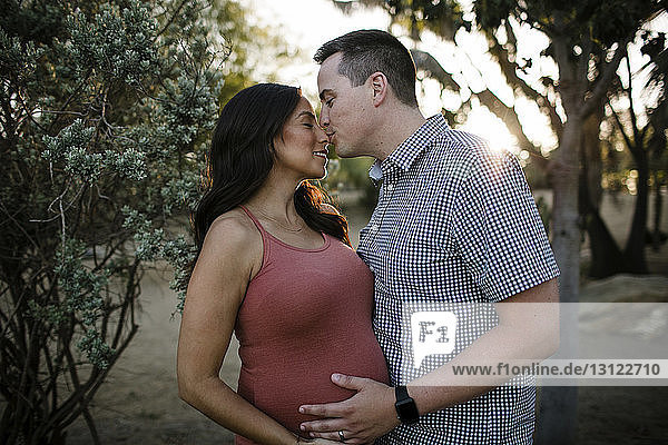 Ehemann küsst schwangere Frau auf die Nase  während er bei Sonnenuntergang im Park steht