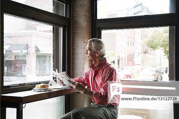 Mature man reading newspaper while having croissant at cafe