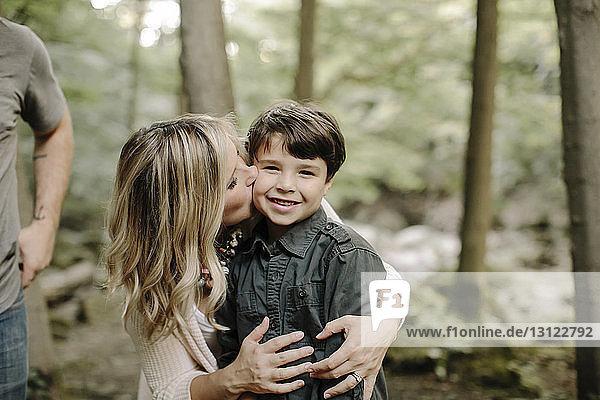 Mutter küsst Sohn  während sie mit Ehemann im Wald steht