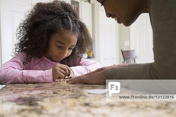 Süßes Mädchen  das zu Hause die Fingernägel seiner Mutter lackiert