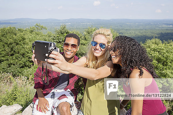 Happy friends taking selfie through instant camera on mountain